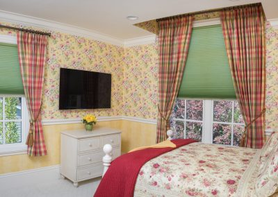 Red, yellow and green plaid drapes with Hunter Douglas honeycomb blinds in a guest bedroom in Newton, MA