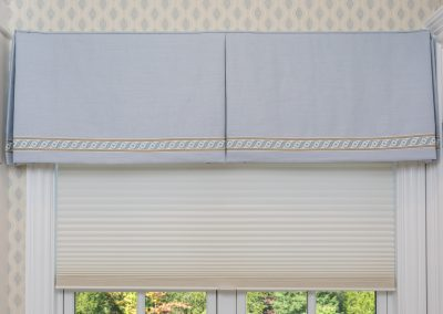 Box-pleated valance with decorative braid trim over a Hunter Douglas semi-opaque honeycomb cordless blind