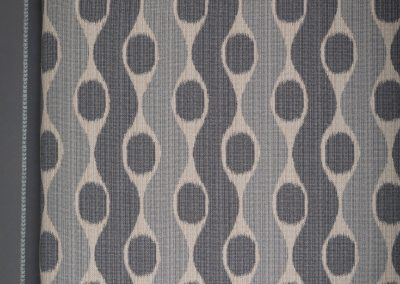 Shades of gray stripe and circle fabric on a padded cornice with decorative cord along top and bottom