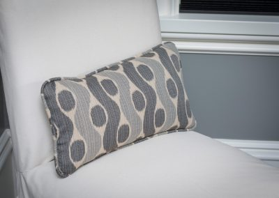 Stripe lumbar pillow on a white slipcover chair