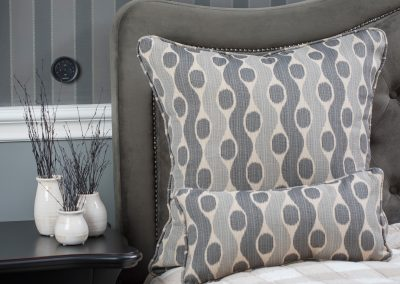 Contemporary bed pillows on a gray suede headboard